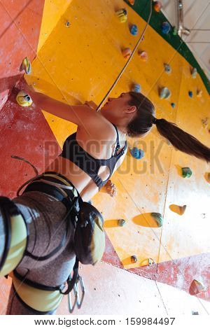 Sport is life. Powerful young active woman training hard in climbing gym while using equipment and climbing up the wall.