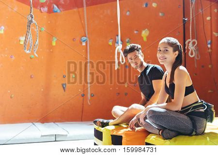 Do it together. Delighted young active couple sittiing in a climbing gym after training and climbing up the wall.