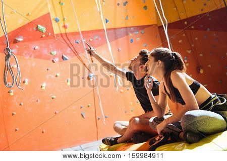 Joyful activity. Happy young active couple sittiing in a climbing gym after training and climbing up the wall.