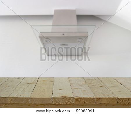 wood table top on blur of hood cooking on white wall for manage smell in kitchen - can use to display or montage on product