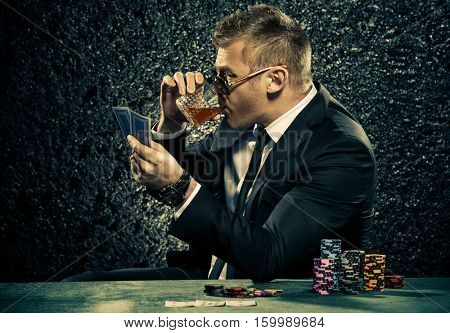 A wealthy mature man drinking brandy and playing poker with the excitement in a casino. Gambling, playing cards and roulette.