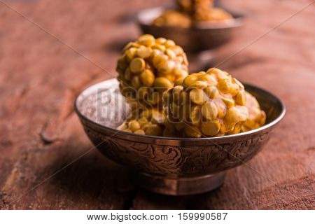 Putnala / futana  / Dalia / Roasted Chickpeas sweet Laddu made up of jaggery or gud or gur in hindi, selective focus