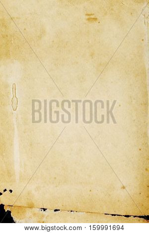 Ancient abstract stained paper background with torn lower part