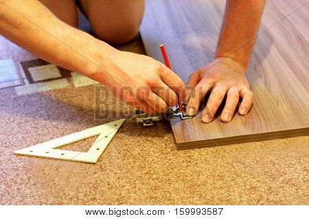 Assembling furniture. The image of a man who with the help of pencil and ruler engaged in the Assembly of furniture.