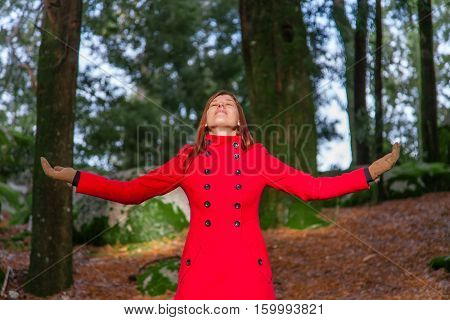 Woman enjoying the warmth of the winter sunlight on a forest wearing a red long coat