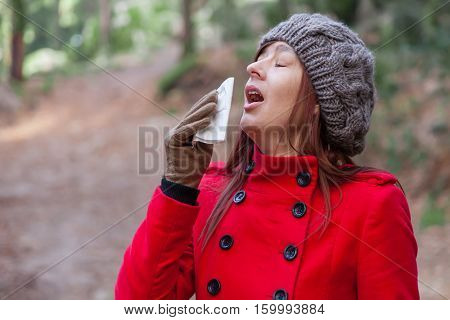 Young woman suffering from a cold, flu or allergies sneezing on a paper handkerchief during winter
