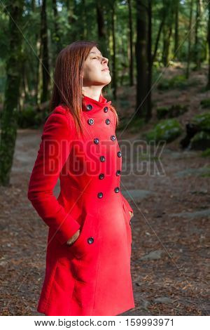 Woman enjoying the warmth of the winter sunlight on a forest wearing a red overcoat
