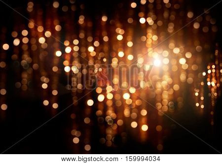 Christmas gold background. Golden holiday glowing backdrop. Defocused Background With Blinking Stars. Blurred Bokeh curtain.