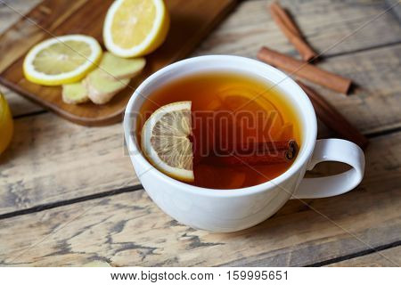 White cup of black natural tea with ginger, lemon and honey. Healthy Antiviral drink. Hot winter useful beverage concept.