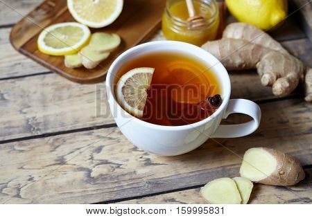 Antiviral ginger tea with lemon, honey and ginger slice on wooden background. Healthy drink. Rustic style. Creative composition.