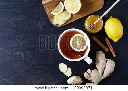 Cup of ginger tea with lemon and honey on dark background. Top view. Antiviral useful Healthy tea. Creative composition.