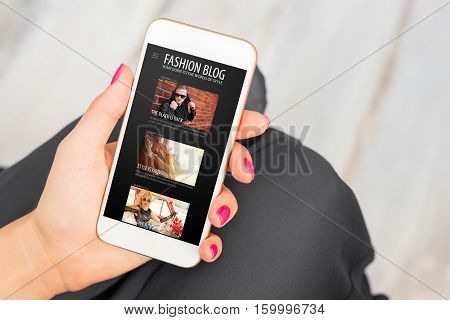 Woman reading fashion blog on mobile phone