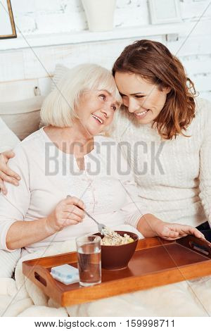 Family bounds. Delighted young beautiful woman taking care of her sick grandmother wo is lying in bed and enjoying her breakfast