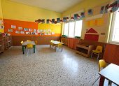 classroom of a childhood nursery with drawings and the tables and small chairs poster