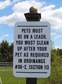 Sign in a public park informing people about the leash law for pets etc. poster