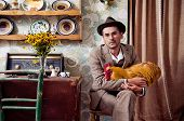 Retro guy sitting and holding his rooster poster