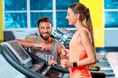 Sports woman making cardio workout on stationary treadmill with personal trainer or friend in the gym with window on the background. poster