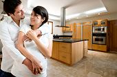 Young happy couple smiling at kitchen of new house poster