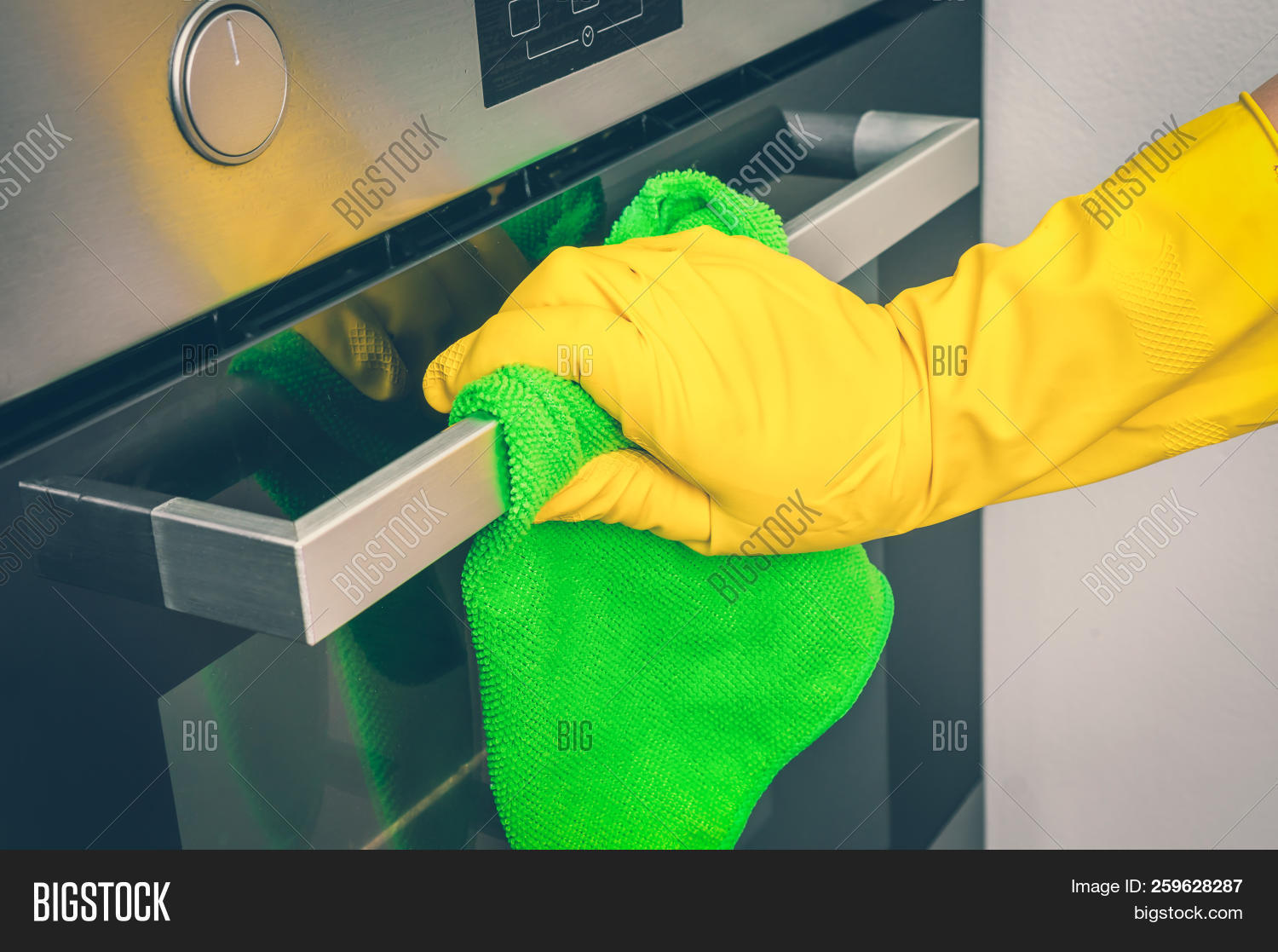 ec31df742c25d Hand In Glove With Green Rag Is Wiping Oven In Kitchen - Housework And Housekeeping  Concept