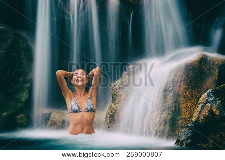 Waterfall woman smiling happy in natural pool. Bikini girl having fun in hawaiian travel destination waterfalls in natural pool. Sexy beautiful girl in pristine nature enjoying summer travel vacation.