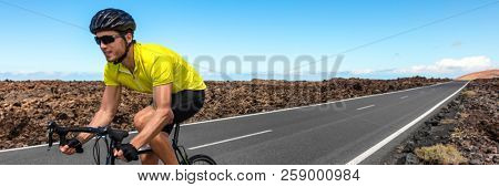 Road biking cyclist man training on bike panorama. Professional cycling athlete riding racing bicycle in competition race on open road. Sports person biking on workout for triathlon.