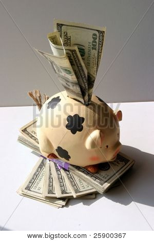 piggy bank overstuffed with $100.00 bills