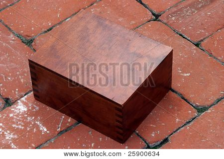 a hand made wooden box on red brick contains a Circa 1889, Model 95, Type II Model 3 Double Derringer