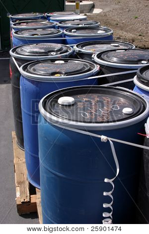 blue plastic 55 gallon drums full of various flammable waste at a recycling plant poster