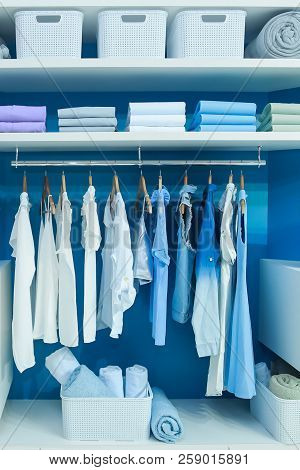 Clean Clothes Hung On Hangers Or Folded On Shelves, Kept On Wardrobe At Home.