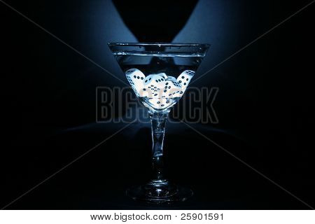"""time laps"" or ""bulb exposure"" of a ""gamblers martini"" with dice in the glass. illuminated with a small flashlight in a pitch black room"