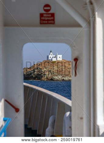 View from ship's door of lighthouse and agios Nikolaos church on rocky land. Kea,Tzia island, Greece. Blue sky background.