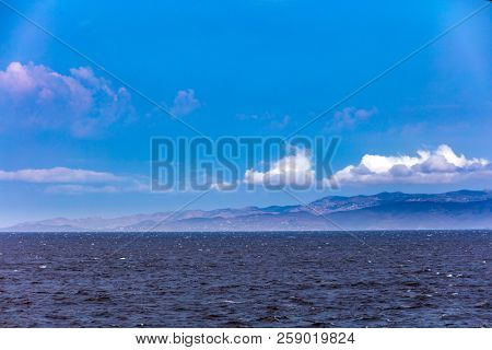Windy day, waves on the sea and blue sky with white clouds. Mountains and greek island background.