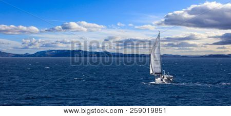 Sailboat travels with wind help, in calm sea. People enjoy the sailing, cloudy sky and mountains background, banner.