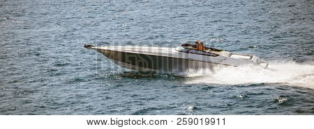 High-speed boat goes fast in calm sea. People enjoy the summer sport in the liquid environment. Panoramic view, banner.