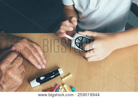 Top View Of A Child Making A Sugar Level With A Glucometer In A Doctor Office. Child Diabetes Concep