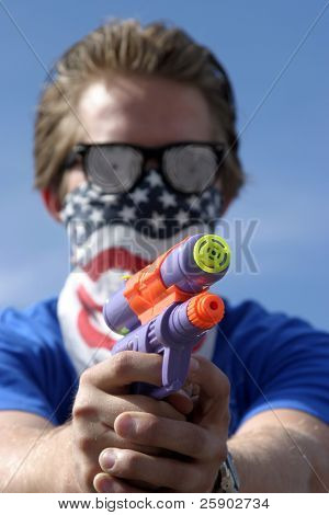 an insane young man wearing Hypnoitic Glasses and an American Flag bandanna holds a Squirt Gun