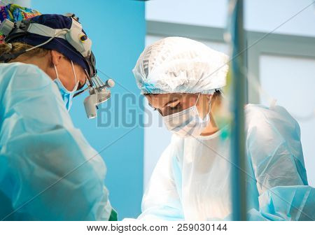 Surgery, Medicine And People Concept - Surgeons In Operating Room At Hospital During Their Work.the