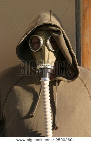 a man in a gas mask trys to hide in an urban warfare enviroment