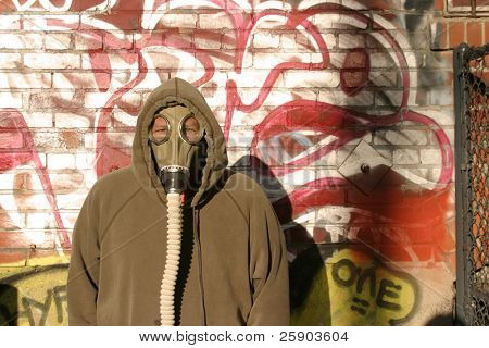 urban camoflauge  a man in a gas mask trys to hide against an urban graffitti wall