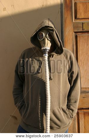man in a gas mask tries to blend in and remain hidden