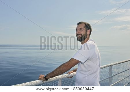 Handsome Man Smiling On The Deck Of A Ship During Holidays.