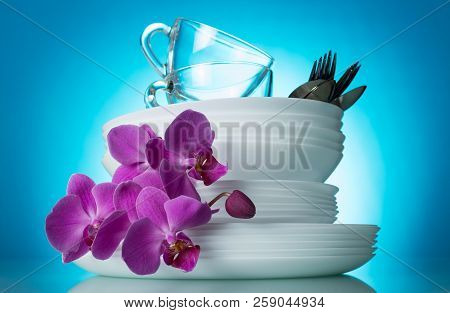 Sparkling Clean White Dishes And A Branch Of An Orchid On Blue Background