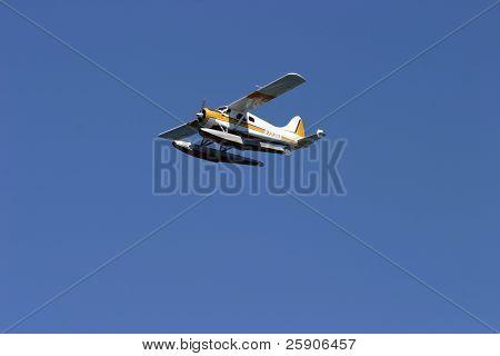 a single engine floatplane flys above Seattle Washington and the pacific northwest.