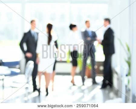 blurred image of business people standing in office.business background