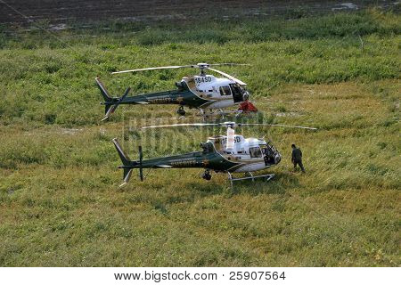 orange county sheriff heliocopters with water buckets attached prepair for flight at a reservoir at the Santiago Canyon wild fires