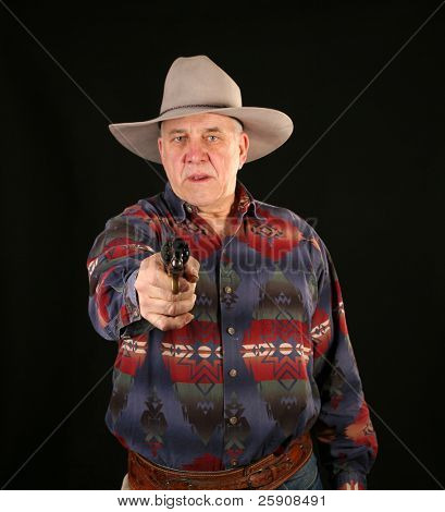 A cowboy points a Colt Navy 44 caliber black powder revolver at YOU THE VIEWER