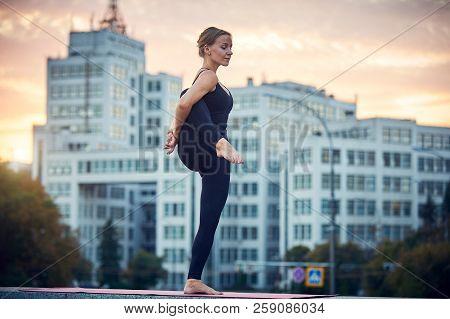 Beautiful Young Woman Practices Yoga Asana Utthita Hasta Padangushthasana -standing On One Leg Pose