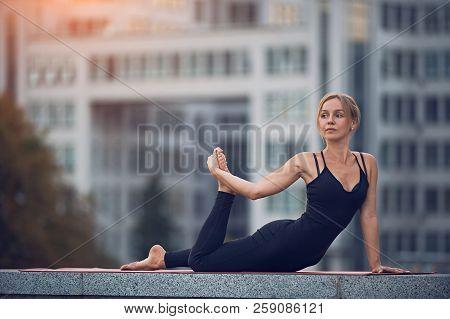 Beautiful Woman Practices Yoga Asana Ardha Bhekasana - Half Frog Pose Outdoors Against The Backgroun