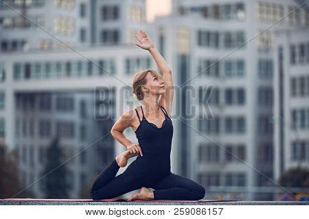 Beautiful Young Woman Practices Yoga Asana One Legged King Pigeon Pose - Eka Pada Rajakapotasana Out