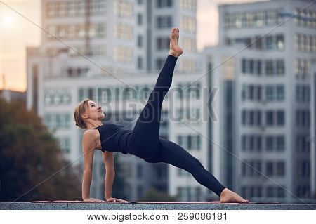 Beautiful Young Woman Practices Yoga Asana Eka Pada Purvottanasana - One Leg Upward Plank Pose Outdo